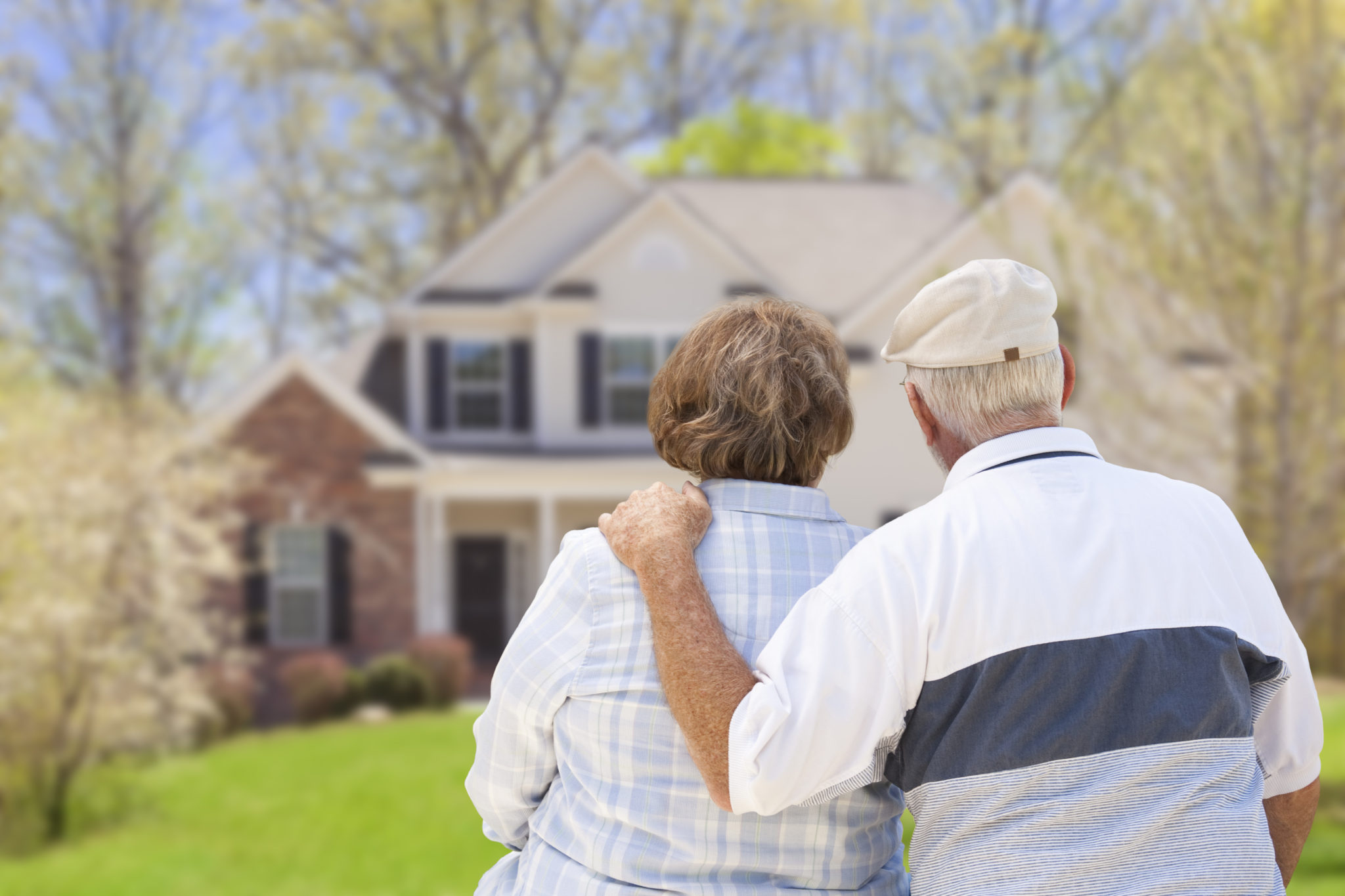 Elderly couple in front of two story house, with backs to camera