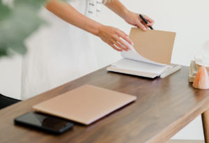 Beige desk with phone, laptop, planner. 3 Unexpected Places to Look for Your Important To-Dos